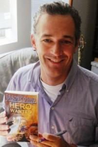 Dan McGirt holds a copy of his book Hero Wanted